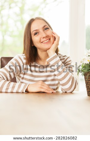 Photo of smiling caucasian woman sitting at the table at home - stock photo