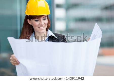 Photo of smiling female constructor with blueprints