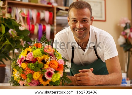 Photo of smiling florist standing next to a colorful bouquet - stock photo