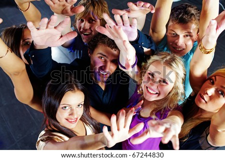 Photo of smiling friends raising arms during the party in excitement - stock photo