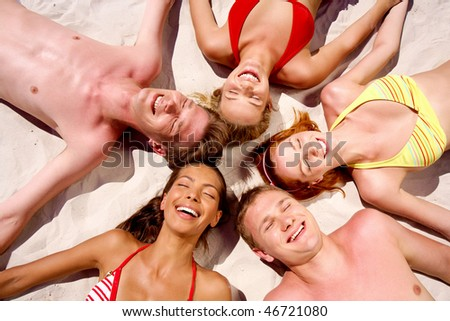 Photo of smiling people lying in the circle on the sand - stock photo