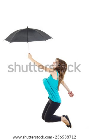Photo of smiling young woman or girl in blue t-shirt and black tights with umbrella jumping in air up studio isolated on white . Carefree and serene happiness concept - stock photo