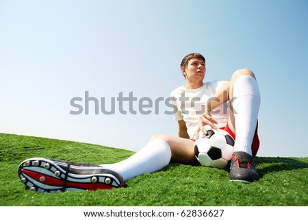 Photo of soccer player sitting on green grass-field and resting - stock photo