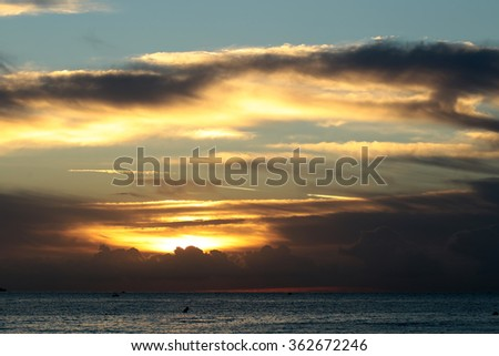 Photo of spectacular marine seashore dark blue sea with ripples against yellow-light illumination of low level cloudy sky at sunset time dusk bleakness over seascape background, horizontal picture - stock photo