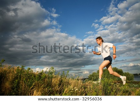 Photo of strong man running along the river - stock photo