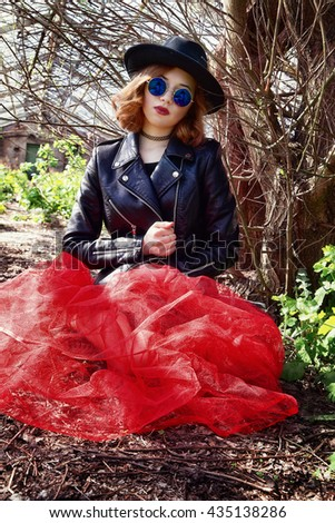 photo of stylish girl in black leather jacket and long skirt
