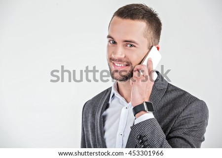 Photo of stylish handsome young man isolated on white background. Man with smart watch using mobile phone - stock photo