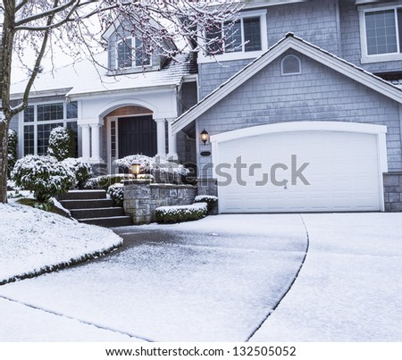 photo of suburban home with snow on drive way, lawn, plants, trees and roof - stock photo