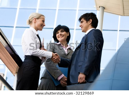 Photo of successful business partners handshaking after striking deal while their colleague looking at them