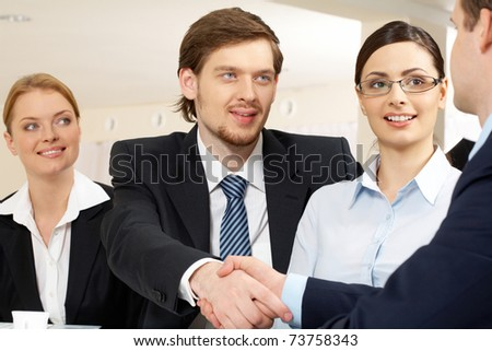 Photo of successful business partners handshaking after striking deal with pretty employees near by - stock photo