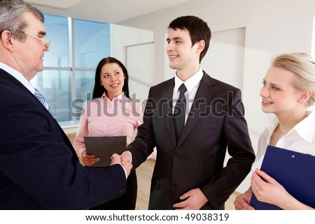 Photo of successful business partners handshaking after striking great deal with happy females near by - stock photo