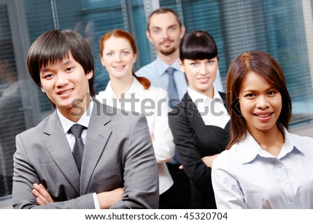 Photo of successful business partners looking at camera with co-workers behind them - stock photo