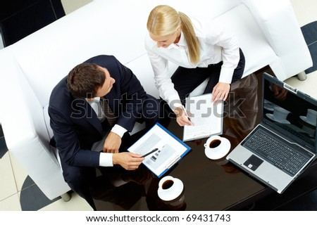 Photo of successful businessman and businesswoman interacting at meeting - stock photo