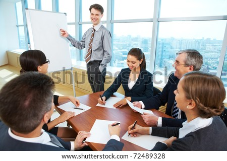 Photo of successful businessman reading lecture to his colleagues at presentation of new project