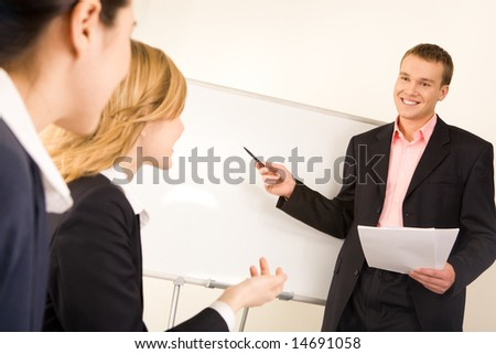 Photo of successful businessman standing at white board while two ladies looking at him during seminar - stock photo