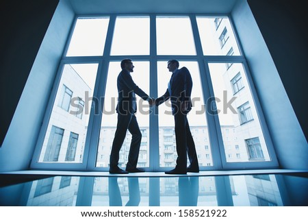 Photo of successful businessmen handshaking after striking deal