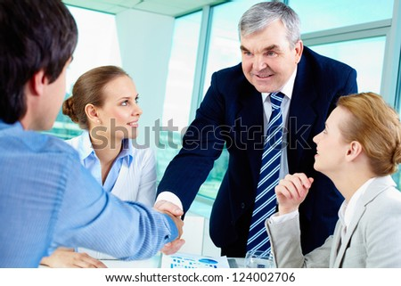 Photo of successful businessmen handshaking after striking deal with partners near by - stock photo