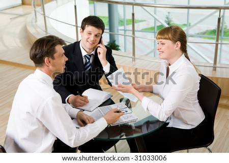 Photo of successful co-workers discussing documents while their partner calling by cellphone at meeting - stock photo