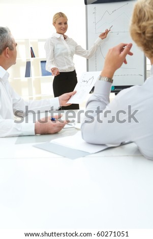 Photo of successful employee standing by whiteboard and presenting project
