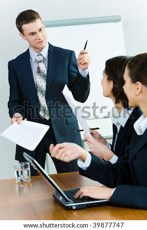 Photo of successful man in suit standing near whiteboard and looking at businesswomen sitting at table and asking him questions