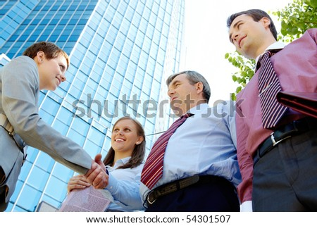 Photo of successful people handshaking after striking deal outdoors at meeting - stock photo