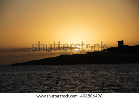 Photo of sunrise on the horizon behind sea at Malta, St. Paul