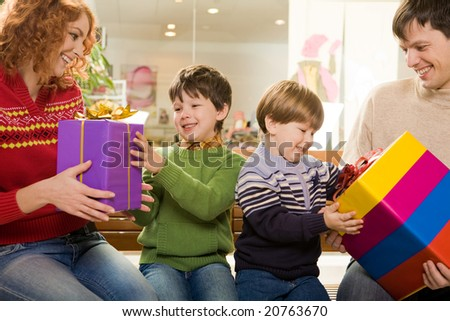 Photo of surprised children being given wonderful gifts by their parents - stock photo