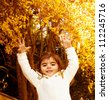 Photo of sweet small girl jumping in autumn forest, lovely female child playing on backyard, adorable little kid in warm sweater with raised hands having fun in fall woods, happy childhood concept - stock photo