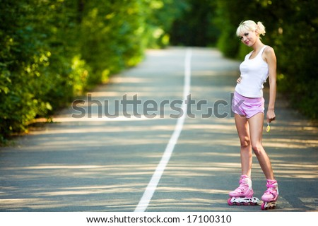 Photo of teenage girl wearing roller skaters while standing on the road in summer