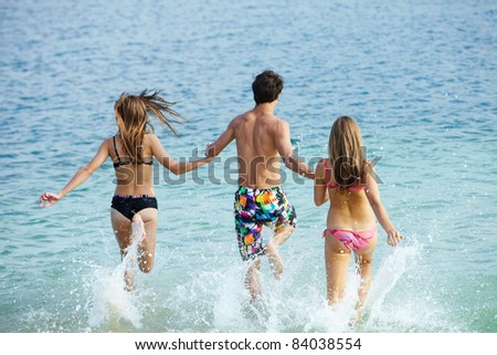 Photo of teenagers running in water while holding each other by hands