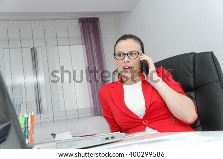 Photo of the Attractive business woman use smart phone and sitting at her worktable with documents and electronic devices - stock photo