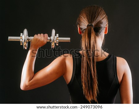 Photo of the back of a young woman doing a shoulder press with a dumbbell over a dark background. - stock photo
