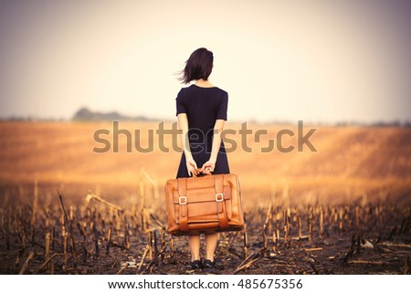photo of the beautiful young woman with suitcase standing in the middle of the field