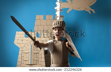 Photo of the boy in medieval knight costume made of cardboards. This decorations are made specially for this photosession by me.  - stock photo