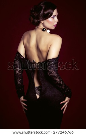 photo of the girl in a black dress with naked back studio