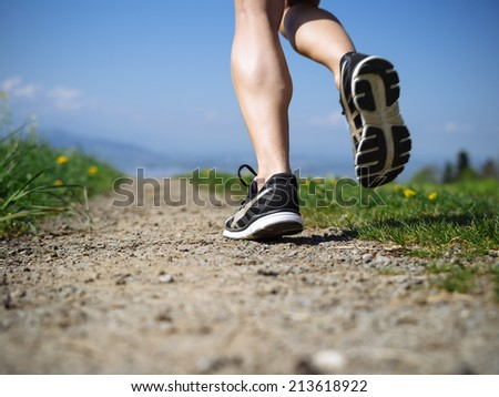 Photo of the legs and shoes of a young woman jogging on a gravel path down a country path. Slight motion blur visible. - stock photo