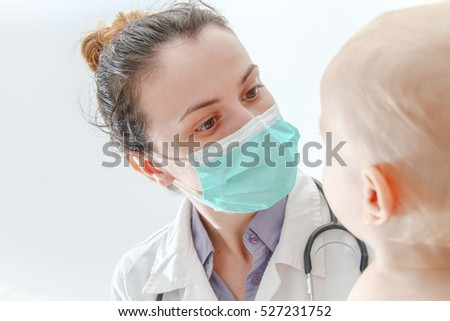 Photo of the One year old sick baby boy at the young female doctor