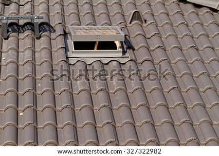 Photo of the roof window on a grey tiled rooftop - stock photo