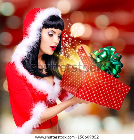 Photo of the surprised  snow maiden looks into the christmas box  with gift in it -  over creative background - stock photo