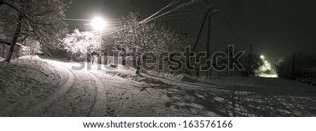 Photo of the village, snow falling on the house, night wintertime landscape - stock photo