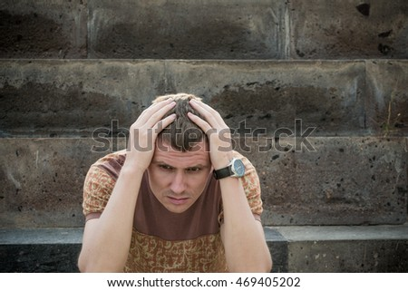 Photo of the Young depressed man with hand on forehead. Crisis, stress concept. Human emotion facial expression
