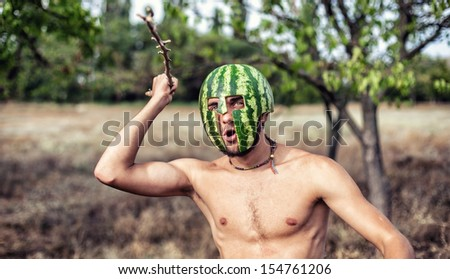 Photo of the young soldier with a water-melon on a head - stock photo