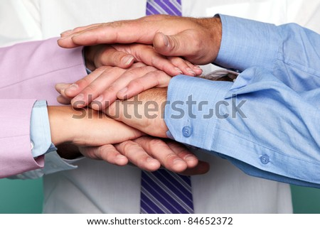Photo of three business people stacking hands to represent teamwork. - stock photo