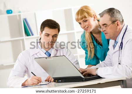 Photo of three colleagues working at new medical project and thinking about it