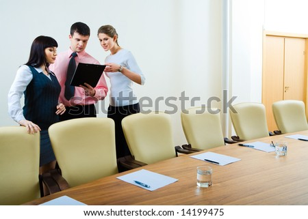 Photo of three confident business partners standing in the office near table and looking at working plan - stock photo