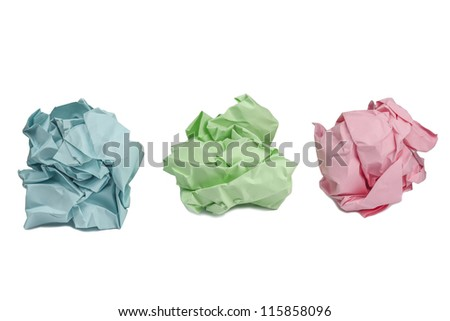 Photo of three crumpled leaves of color paper on a white background