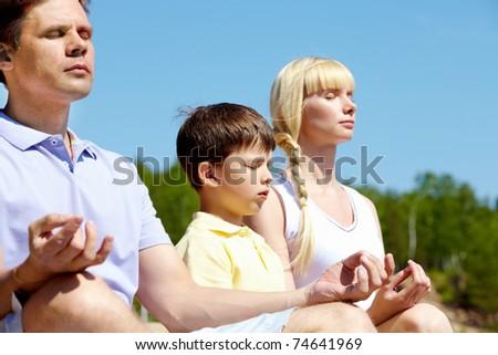 Photo of three family members meditating on summer day outdoors - stock photo