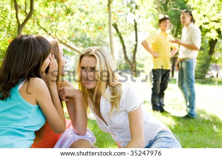 Photo of three girls whispering around each other and looking at guys on background - stock photo