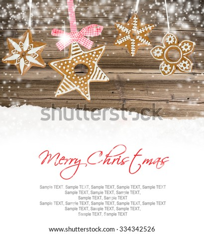 Photo of traditional Christmas sweets on wooden board with snow and white space fot text