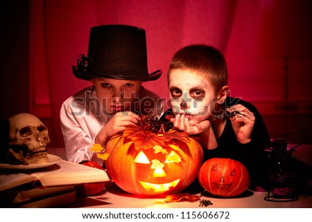 Photo of twin eerie boys looking at camera in dark - stock photo